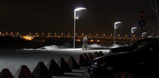 Человек бежит по ночному городу в свете фонарей
