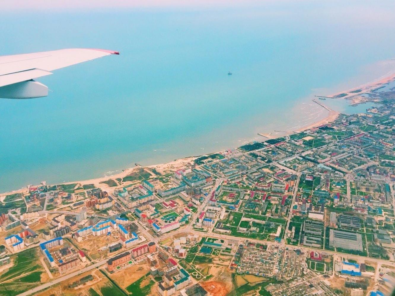 Каспийск из окна взлетающего самолёта, в трёх километрах от берега в море виднеется цех №8 завода «Дагдизель»
